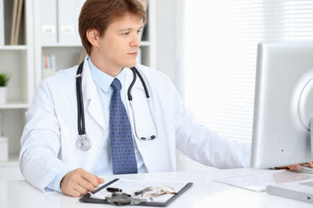 Friendly male doctor is sitting at the table and working in the hospital office. Ready to examine and help patients. High level and quality medical service concept.