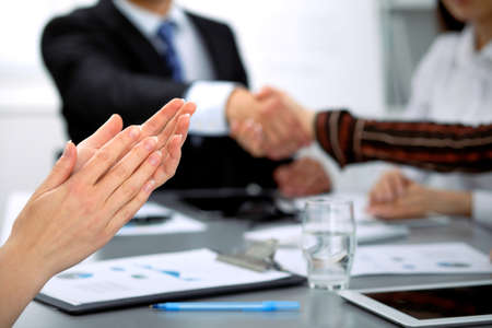 unanimous: Close up of female applause while business people shaking hands at meeting Stock Photo