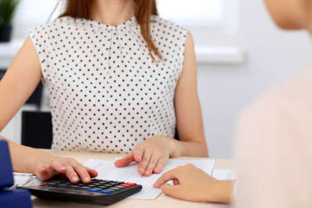 Two female accountants counting on calculator income for tax form completion hands closeup. Planning budget, audit concept. Stock Photo