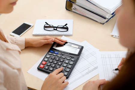Two female accountants counting on calculator income for tax form completion hands closeup. Internal Revenue Service inspector checking financial document. Planning budget, audit  concept Foto de archivo