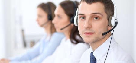 Call center operators. Focus op zakenman in de headset tijdens het raadplegen van klanten