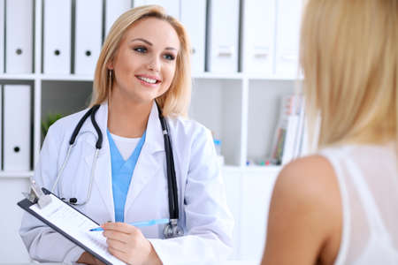 Doctor and  patient  discussing something while phisician pointing into medical history form at clipboard