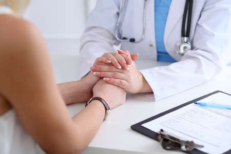 Close up of doctor hands reassuring her female patient