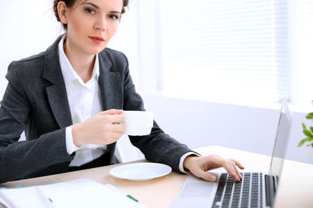Business woman with a cup of coffee is sitting at the table and typing on a laptop computer in the white colored office .