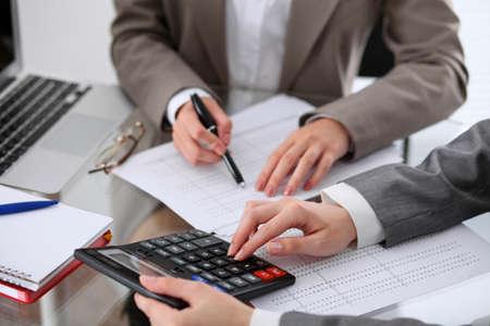 Twee vrouwelijke accountants rekenen op calculator inkomen voor belastingformulier afronding handen close-up. Internal Revenue Service Inspector controleert financieel document. Planning budget, audit concept Stockfoto