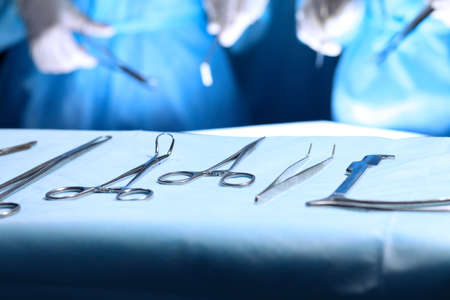 Surgical tools lying on the table while group of surgeons at background operating patient. Steel medical instruments ready to be used Stock Photo