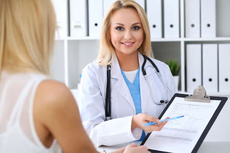 hospital patient: Doctor and  patient  discussing something while physician pointing into medical history form at clipboard Stock Photo