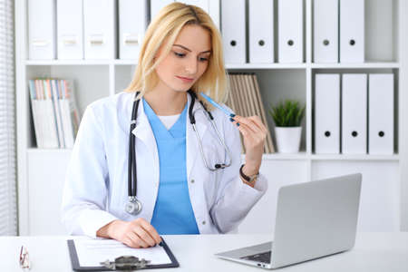 Doctor woman filling up medical form while  sitting at the desk. Medicine and health care concept