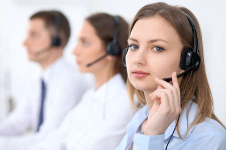 Call center operators. Focus at young beautiful business woman in headset