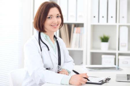 Jonge brunette vrouwelijke arts zit aan de tafel en werkt op ziekenhuis kantoor.