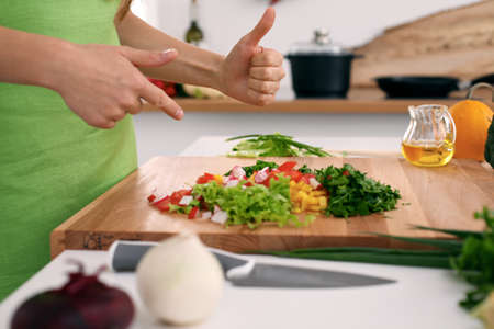 Close up of womans hands cooking in the kitchen. Housewife offering fresh salad with thumbs up. Vegetarian and healthily cooking concept. Stock Photo