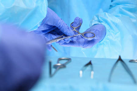 Close-up of of surgeons hands at work in operating theater toned in blue