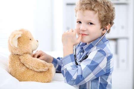 Kind Patient afrer Gesundheit Prüfung spielen als Arzt mit Stethoskop und Teddybär