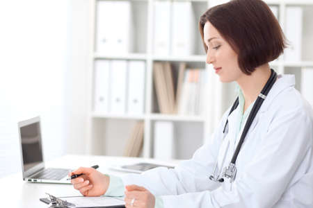 Young brunette female doctor sitting at the table and working at hospital office. Stock Photo