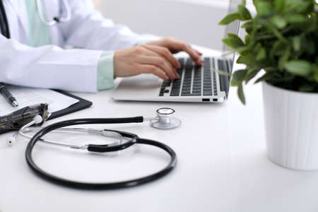 Close-up of stethoscope lying next to a laptop and nearby a plant