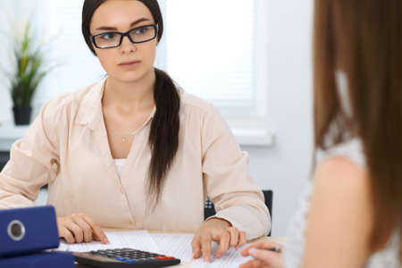 Two female accountants counting on calculator income for tax form completion hands closeup. Internal Revenue Service inspector checking financial document. Planning budget, audit  concept Stock Photo