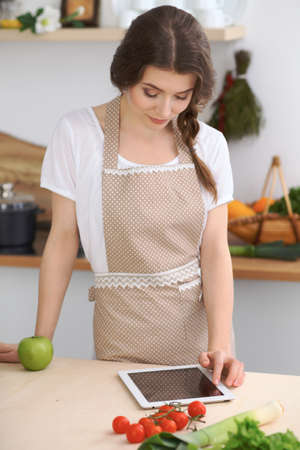 chose: Young brunette woman is cooking in the kitchen. Housewife chooses the best recipe using touchpad computer. Concept of healthy meal and vegetarian lifestyle