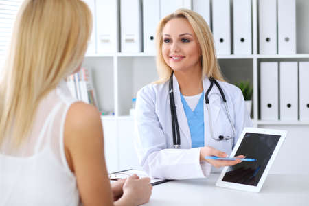 Doctor and patient discussing something while physician pointing into touch pad computer