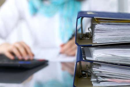 Bindmiddelen met papieren wachten om te worden verwerkt met zakenvrouw of secretaresse terug in vervaging. Internal Revenue Service inspecteur die het financiële document controleert. Stockfoto - 86440945