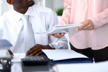 African american bookkeeper or financial inspector  making report, calculating or checking balance. Internal Revenue Service checking financial document. Audit concept. Stock Photo