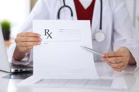 Vrouwelijke geneeskunde arts hand houden klembord pad en voorschrift geven aan de patiënt close-up. Panacea en levensredding, voorschrijven behandeling, legale drugstore, contraceptie concept Stockfoto - 86385211