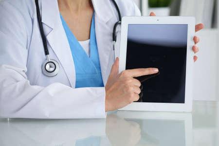 Vrouwelijke arts die in tabletcomputer, close-up van handen richt. Arts klaar om te onderzoeken en de patiënt te helpen. Geneeskunde, gezondheidszorg en hulpconcept. Stockfoto