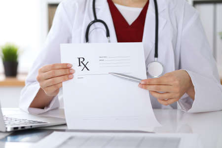 Vrouwelijke geneeskunde arts hand houden klembord pad en voorschrift geven aan de patiënt close-up. Panacea en levensredding, voorschrijven behandeling, legale drugstore, contraceptie concept Stockfoto - 86385314