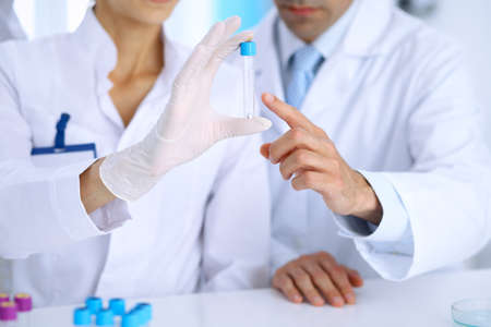 Team of  scientific researchers in laboratory studying substances or blood sample. New vaccine for pharmacology industry is s almost ready. Medicine and science concept. Stock Photo