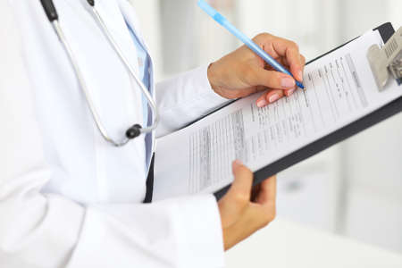 Close-up of a female doctor filling  up medical form at clipboard while standing straight in hospital.