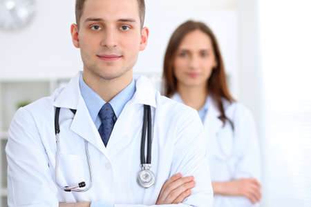 Friendly male doctor on the background of female physician in hospital office. Ready to examine and help patients. High level and quality medical service concept. Best treatment and patient care concept Stock Photo