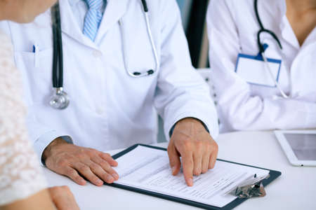 hospital patient: Doctor and  patient talking while sitting at the desk in office. Physician pointing into medical history form. Medicine and health care concept. Stock Photo