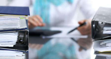 Bindmiddelen met papieren wachten om te worden verwerkt met zakenvrouw of secretaresse terug in vervaging. Internal Revenue Service inspecteur die het financiële document controleert. Stockfoto
