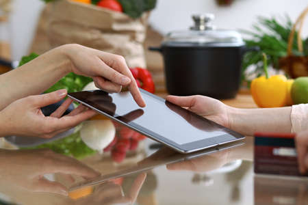 Close-up of human hands pointing into tablet  in the kitchen. Friends having fun while choosing menu or making online shopping.  Cooking, healthy meal and friendship concept.