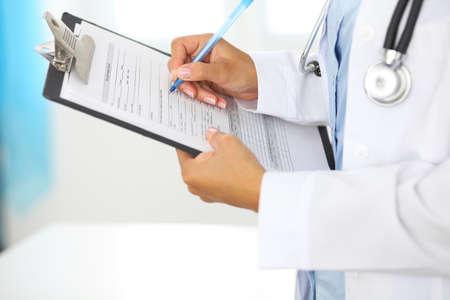 Primer plano de un médico femenino llenando formulario médico en el portapapeles mientras está de pie recto en el hospital. Foto de archivo