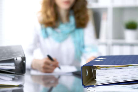 Binders with papers are waiting to be processed with businesswoman or secretary back in blur. Internal Revenue Service inspector checking financial document. Banco de Imagens