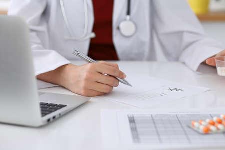 Female medicine doctor fills up prescription form to patient closeup. Panacea and life save, prescribe treatment, legal drug store, contraception concept. Stock Photo