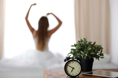 Alarm clock standing on bedside table has already rung early morning to wake up woman is stretching in bed in background. Early awakening, not getting enough sleep, oversleep concept.