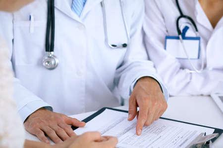 Doctor y paciente hablando mientras está sentado en el escritorio en la oficina. Médico apuntando a formulario de historia médica. Concepto de medicina y salud. Foto de archivo