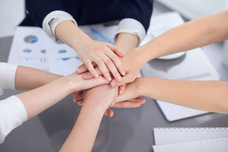 Unknown business people joining hands, close-up. Teamwork concept.