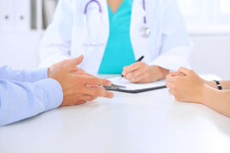 Doctor and patient couple are discussing something, just hands at the table.