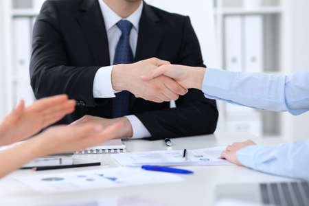 Unknown business people shaking hands, finishing up a meeting, close-up Stock Photo