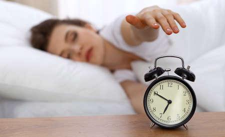 目覚まし時計で目を覚ますしようとベッドで休んで眠っている美しい女性。
