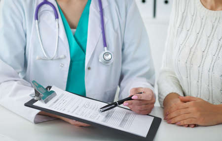 Doctor and patient, close-up of hands.  Physician talking about medical examination results. Medicine, healthcare and helping concept Stock Photo