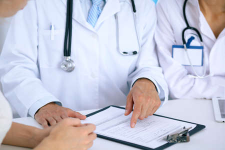 hospital patient: Doctor and  patient talking while sitting at the desk in office. Physician pointing into medical history form. Medicine and health care concept Stock Photo