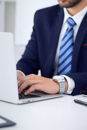 Businessman working by typing on laptop computer. Mans hands on notebook or business person at workplace. Employment  or start-up concept