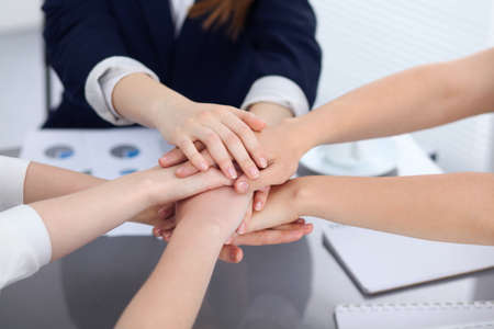 manos unidas: Unknown business people joining hands, close-up. Teamwork concept