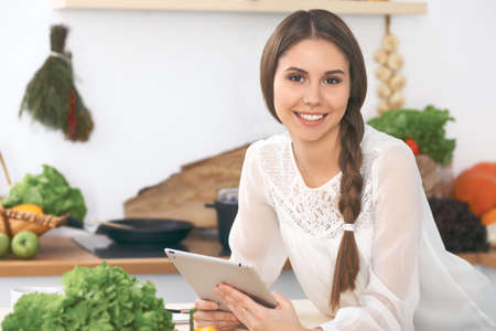 Young  woman using tablet while cooking or making online shopping in kitchen Foto de archivo