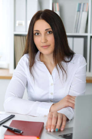 Young beautiful business woman or confident female accountant in office. Student girl during exam preparing. Audit, tax service or education concept