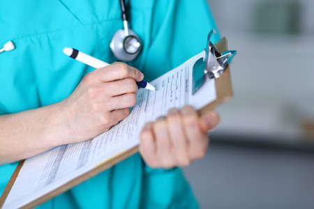 Female doctor filling up medical form on clipboard closeup.  Physician finish up examining his patient in hospital and ready to give a prescription to help. Healthcare, insurance and medicine concept Foto de archivo