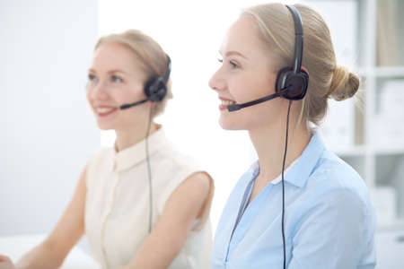 Image of bright call center. Focus on young beautiful woman in a headset